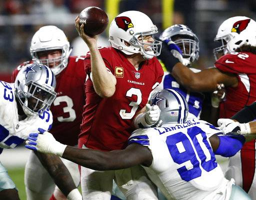 FILE - In this Sept. 25, 2017, file photo, Arizona Cardinals quarterback Carson Palmer (3) is sacked by Dallas Cowboys defensive end Demarcus Lawrence (90) during the second half of an NFL football game, in Glendale, Ariz. While sack totals are usually about the individual, pass rushers and their coaches like to think getting the quarterback to the ground has a lot to do with what's going on around the sack stars.(AP Photo/Ross D. Franklin, File)