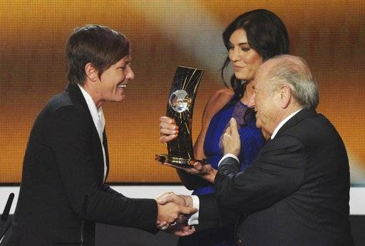 "FILE - In this Jan. 7, 2013, file photo, Abby Wambach, left, of the United States is presented the FIFA Women's World Player of the Year award by Hope Solo, center, goalkeeper of the U.S. team, and FIFA President Sepp Blatter, right, during the FIFA Ballon d'Or Gala held at the Kongresshaus in Zurich, Switzerland. Solo told a Portuguese newspaper that former FIFA President Blatter sexually assaulted her at the ceremony. In an interview published Friday, Nov. 10, 2017, in the newspaper Expresso, Solo said Blatter ""grabbed� her inappropriately on her rear end shortly before the two appeared onstage at the awards event."