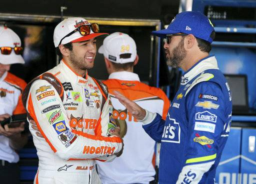 Chase Elliott, left, and Jimmie Johnson talk inside the garage area before practice for the NASCAR Cup Series auto race at Phoenix International Raceway, Friday, Nov. 10, 2017, in Avondale, Ariz. Both drivers are looking to fill the final spot for the Championship 4. (AP Photo/Ralph Freso)