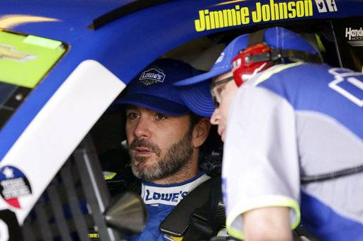Jimmie Johnson, left, talks to a crew member in the garage during a practice session for Sunday's NASCAR Cup series auto race at Texas Motor Speedway in Fort Worth, Texas, Friday, Nov. 3, 2017.
