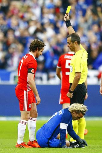Referee, Manuel Jorge Neves Moreira de Sousa of Portugal, gives a yellow card to Wales' Joe Allen for a tackle on France's Antoine Griezmann, on ground, during an international friendly soccer match between France and Wales at Stade de France in Saint Denis, a northern suburb of Paris, France, Friday, Nov. 10, 2017.