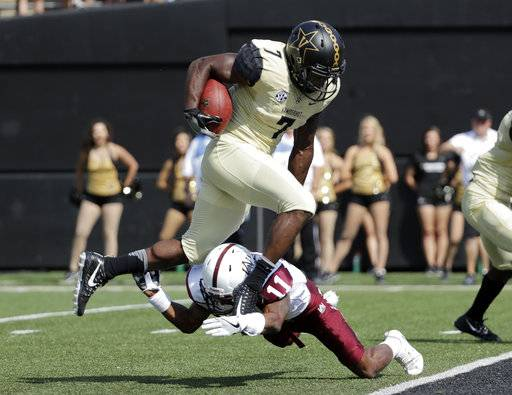 FILE -- In this Sept. 9, 2017 file photo, Vanderbilt running back Ralph Webb (7) jumps over Alabama A&M defensive back Harvey Harris (11) on his way to scoring a touchdown in an NCAA college football game in Nashville, Tenn. Kentucky can't help but wonder what might have been if not for a pair of close losses that separates the Wildcats from an 8-1 record. It's the kind of disappointment the Wildcats will have to forget Saturday when they visit Vanderbilt.
