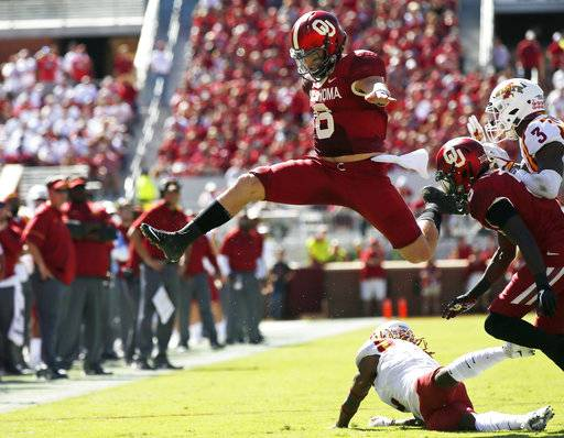 FILE - In this Oct. 7, 2017, file photo, Oklahoma quarterback Baker Mayfield (6) leaps over Iowa State defensive back De'Monte Ruth, bottom, in the second quarter of an NCAA college football game in Norman, Okla. The outright lead in in the Big 12 Conference is on the line when No. 5 Oklahoma hosts No. 8 TCU on Saturday
