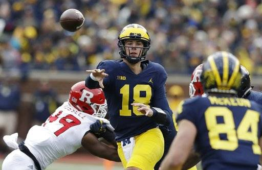 FILE - In this Oct. 28, 2017, file photo, Michigan quarterback Brandon Peters (18) throws while pressured by Rutgers linebacker Brandon Russell (49) during the second half of an NCAA college football game in Ann Arbor, Mich. In his first career start last week, Peters went 8 for 13 for 56 yards a touchdown against Minnesota. More importantly, he directed an offense that put up 33 points in a lopsided victory. Michigan plays Maryland this week.