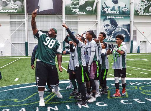 This photo provided by newyorkjets.com shows New York Jets NFL football nose tackle Mike Pennel, left, taking a selfie with the winning team after a flag football tournament at the Jets training center in Florham Park, N.J., Tuesday, Nov. 7, 2017. (newyorkjets.com via AP)