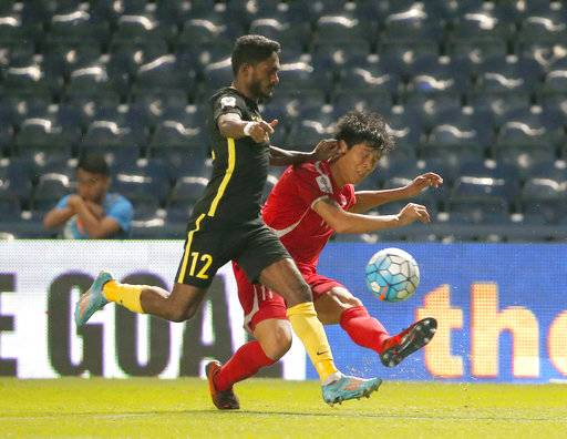 Malaysia's Kunanlan Subramaniam, left, and North Korea's Jong IL Gwan battle for the ball during their Asian Cup qualifiers soccer match at Thunder Castle stadium in Buriram province, Thailand, Friday, Nov. 10, 2017. North Korea beat Malaysia 4-1 .