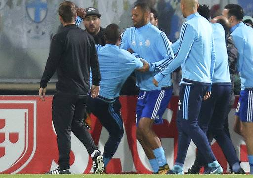 FILE - In this Thursday, Nov. 2, 2017 file photo, Marseille's Patrice Evra, third left, raises his foot trying to kick a man during a scuffle with Marseille supporters who trespassed onto the field before the Europa League group I soccer match between Vitoria SC and Olympique de Marseille at the D. Afonso Henriques stadium in Guimaraes, Portugal. UEFA has suspended Marseille defender Patrice Evra until June 2018 for kicking one his own team's fans before a Europa League game.