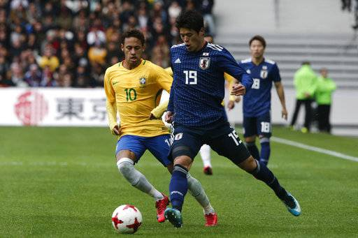 Brazil's Neymar, left, fight s for the ball with Japan's Hiroki Sakai during their international friendly soccer match Brazil against Japan at the Pierre Mauroy stadium in Lille, northern France, Friday, Nov. 10, 2017.