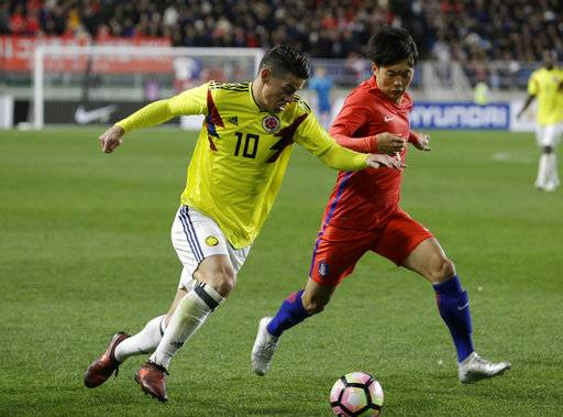 Colombia's James Rodriguez, left, fights for the ball against South Korea's Kim Jin-su during their friendly soccer match at Suwon World Cup Stadium in Suwon, South Korea, Friday, Nov. 10, 2017.