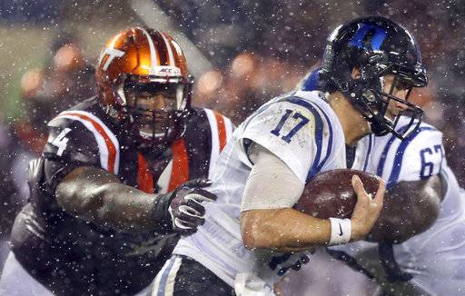 Virginia Tech defender Tim Settle (4) grabs Duke quarterback Daniel Jones (17) from behind in the second half of an NCAA college football game in Blacksburg Va., Saturday, Oct. 28, 2017. Virginia Tech won the game 24-3. (Matt Gentry/The Roanoke Times via AP)
