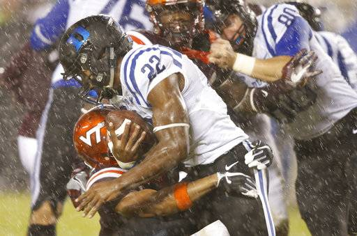 Duke running back Brittain Brown (22) slips past Virginia Tech defensive back Mook Reynolds (6) in the rain during the second half of an NCAA college football game in the rain in Blacksburg, Va., Saturday, Oct. 28, 2017.