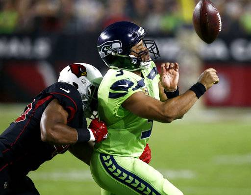 Seattle Seahawks quarterback Russell Wilson (3) loses the ball out of bounds as he is hit by Arizona Cardinals inside linebacker Haason Reddick (43) during the second half of an NFL football game, Thursday, Nov. 9, 2017, in Glendale, Ariz.