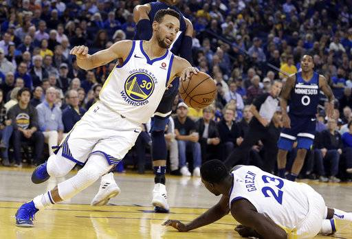 Golden State Warriors' Stephen Curry, left, drives the ball up court around Draymond Green (23) during the first half of an NBA basketball game against the Minnesota Timberwolves on Wednesday, Nov. 8, 2017, in Oakland, Calif.