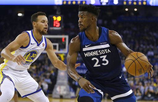Minnesota Timberwolves' Jimmy Butler, right, drives the ball against Golden State Warriors' Stephen Curry (30) during the first half of an NBA basketball game Wednesday, Nov. 8, 2017, in Oakland, Calif.