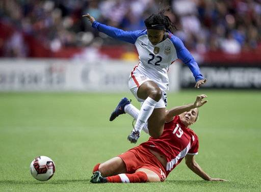 Canada's Adriana Leon (19) slides to take the ball away from the United States' Taylor Smith (22) during the second half of an international friendly soccer match, Thursday, Nov. 9, 2017, in Vancouver, British Columbia. (Darryl Dyck/The Canadian Press via AP)