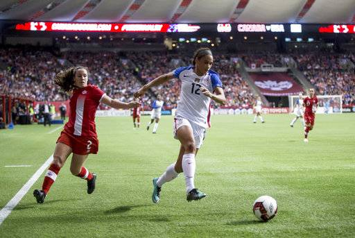United States' Lynn Williams (12) moves the ball past Canada's Allysha Chapman (2) during the second half of an international friendly soccer match, Thursday, Nov. 9, 2017, in Vancouver, British Columbia. (Darryl Dyck/The Canadian Press via AP)