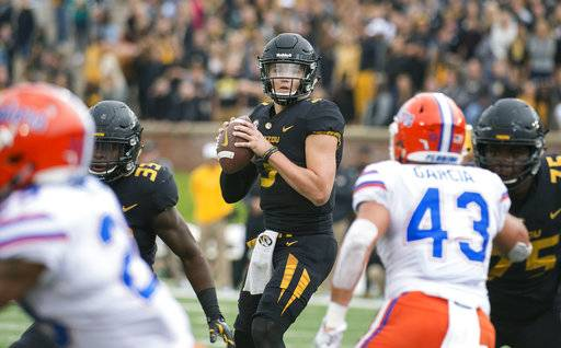 FILE - In this Nov. 4, 2017, file photo, Missouri quarterback Drew Lock looks for an open receiver between Florida defenders during the first half of an NCAA college football game in Columbia, Mo. Missouri (4-5, 1-4) is building off of a 45-16 trouncing of Florida last weekend. Lock threw for 228 yards, three touchdowns and an interception on 15-for-20 passing in the win, and the Tigers rushed for 227 yards. Missouri plays Tennessee this week.