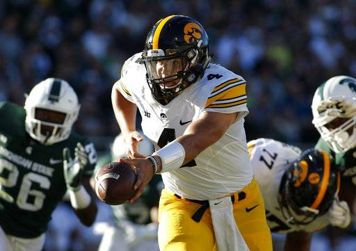 FILE - In this Sept. 30, 2017, file photo, Iowa quarterback Nate Stanley, center, looks to hand off against Michigan State's Brandon Randle, left, and Raequan Williams, right, during the second quarter of an NCAA college football game in East Lansing, Mich. Stanley is playing well, just in time for a trip back to his home state. Stanley, who grew up in Menomonie, Wis., had five touchdown passes against the Buckeyes las weekend.