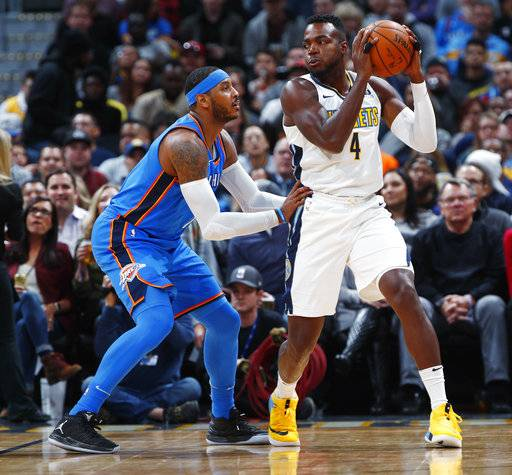Oklahoma City Thunder forward Carmelo Anthony, left, defends Denver Nuggets forward Paul Millsap during the first half of an NBA basketball game Thursday, Nov. 9, 2017, in Denver.