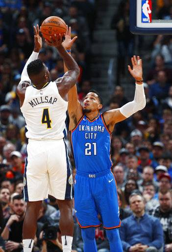 Denver Nuggets forward Paul Millsap, left, goes up for a shot over Oklahoma City Thunder guard Andre Roberson during the first half of an NBA basketball game Thursday, Nov. 9, 2017, in Denver.