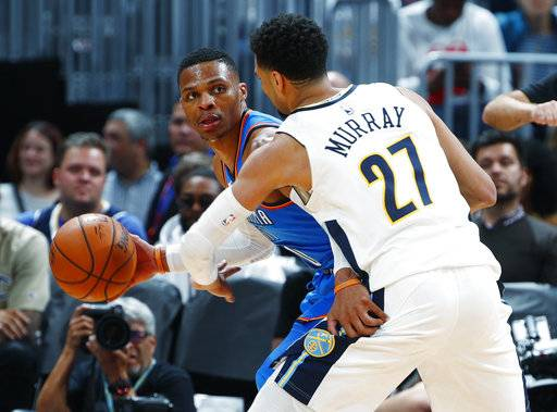 Oklahoma City Thunder guard Russell Westbrook, left, looks to pass the ball as Denver Nuggets guard Jamal Murray defends during the second half of an NBA basketball game Thursday, Nov. 9, 2017, in Denver. The Nuggets won 102-94.