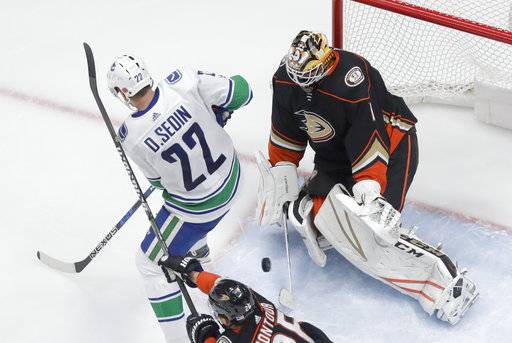 Anaheim Ducks goalie Reto Berra, right, blocks a shot by Vancouver Canucks left wing Daniel Sedin during the third period of an NHL hockey game in Anaheim, Calif., Thursday, Nov. 9, 2017. The Ducks won 4-1.