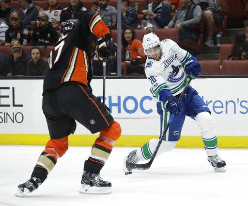 Vancouver Canucks center Brandon Sutter, right, shoots past Anaheim Ducks defenseman Hampus Lindholm during the first period of an NHL hockey game in Anaheim, Calif., Thursday, Nov. 9, 2017.