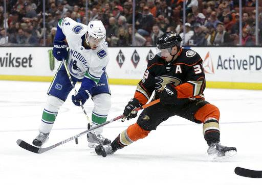 Vancouver Canucks defenseman Michael Del Zotto, left, works against Anaheim Ducks right wing Jakob Silfverberg for the puck during the first period of an NHL hockey game in Anaheim, Calif., Thursday, Nov. 9, 2017.