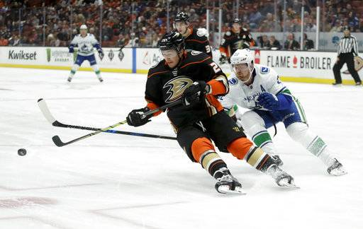 Vancouver Canucks left wing Daniel Sedin, right, knocks the puck away from Anaheim Ducks defenseman Brandon Montour during the first period of an NHL hockey game in Anaheim, Calif., Thursday, Nov. 9, 2017.