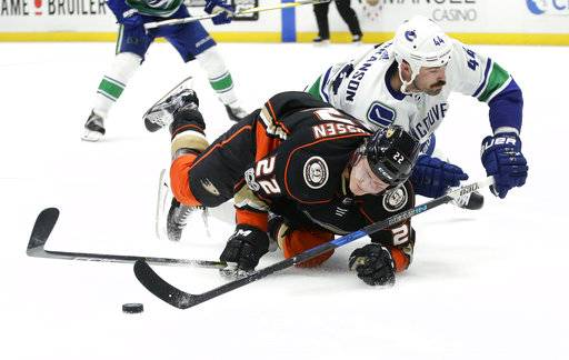 Anaheim Ducks center Dennis Rasmussen, left, competes against Vancouver Canucks defenseman Erik Gudbranson for the puck during the second period of an NHL hockey game in Anaheim, Calif., Thursday, Nov. 9, 2017.