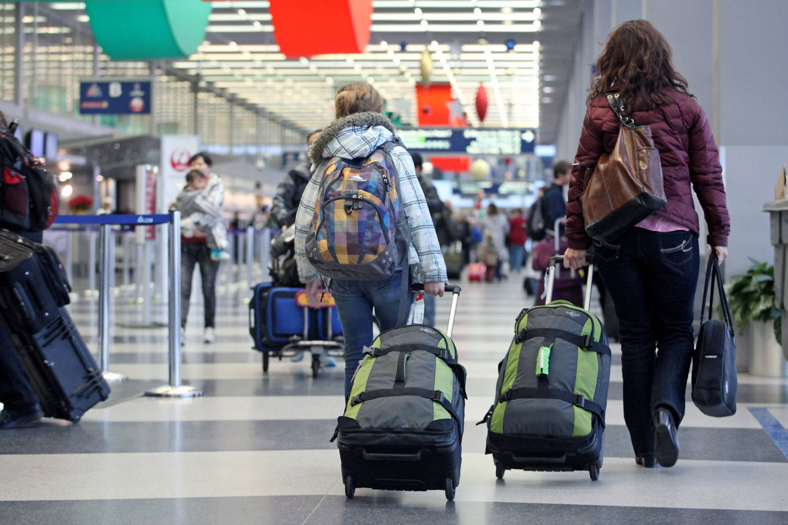 Travelers pull their luggage through O'Hare International Airport in Chicago. As the holidays approach, don't forget about etiquette when it comes to your luggage.