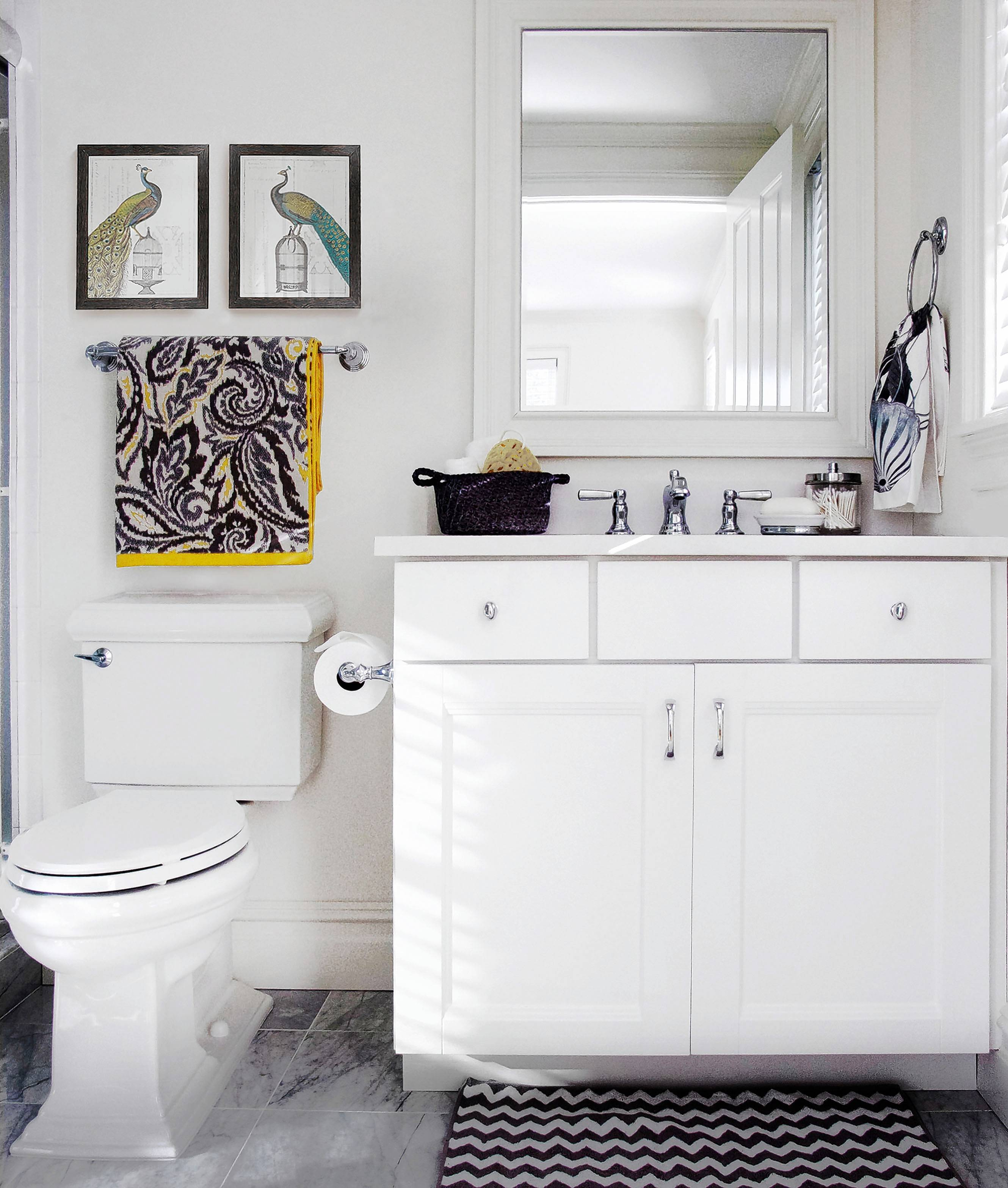 Painting bathrooms white with white cabinets allows you to decorate with fun and vibrant accessories such as towels, art, baskets and canisters.
