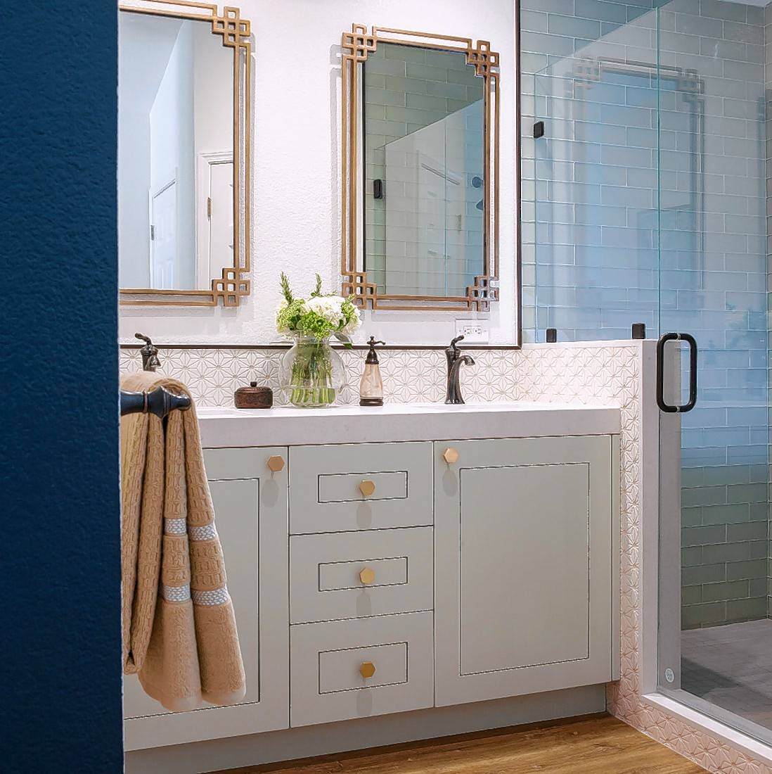 The San Jose bathroom uses a boldly painted blue alcove around the toilet for a pop of color in a master bath composed of muted whites and greens.