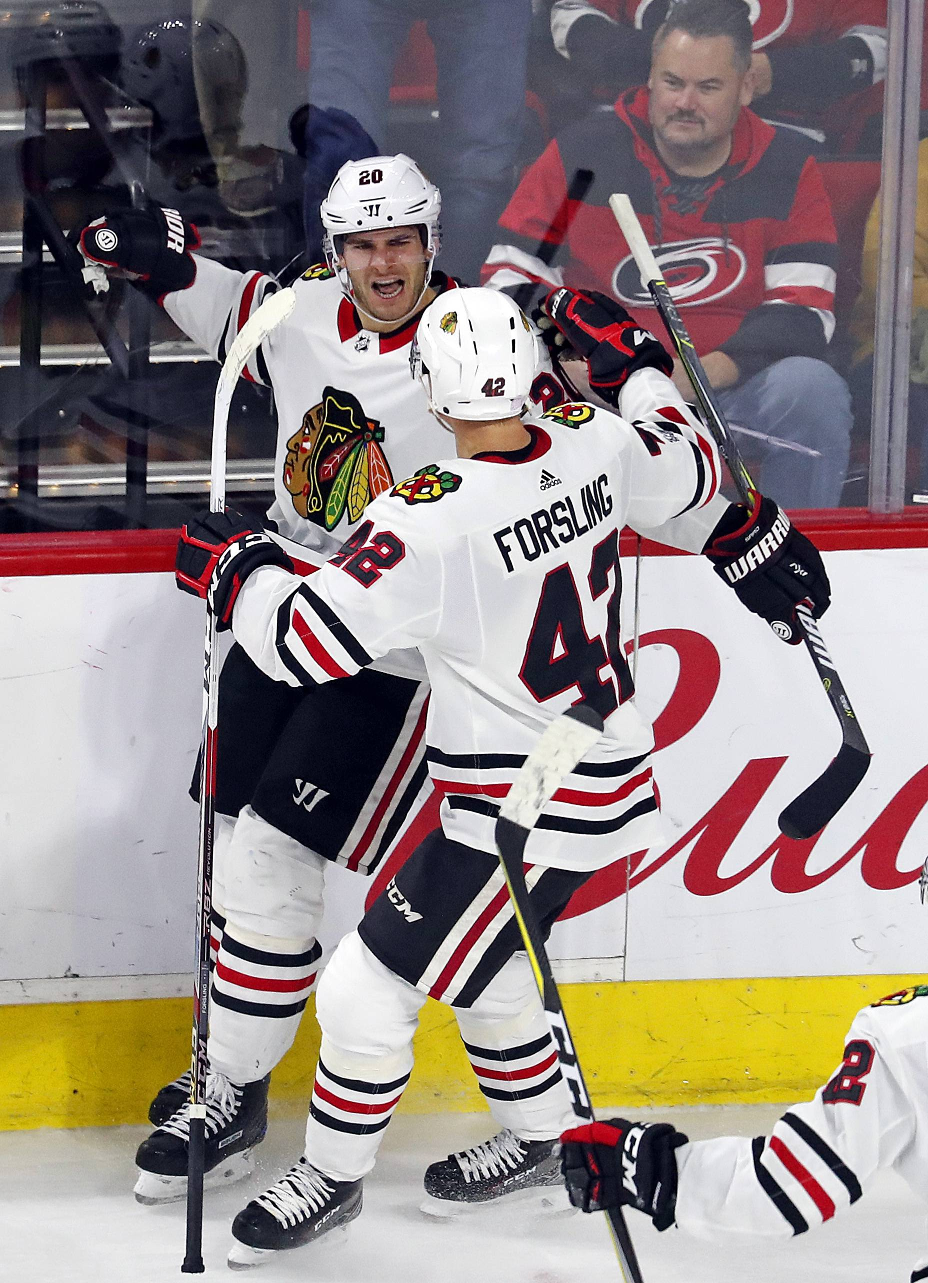 Chicago Blackhawks' Brandon Saad (20) celebrates his winning goal against the Carolina Hurricanes with teammate Gustav Forsling (42) during the overtime period of an NHL hockey game, Saturday, Nov. 11, 2017, in Raleigh, N.C.