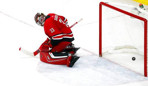 Chicago Blackhawks' Brandon Saad's shot goes through the legs of Carolina Hurricanes goalie Scott Darling (33) to win an NHL hockey game in overtime Saturday, Nov. 11, 2017, in Raleigh, N.C.
