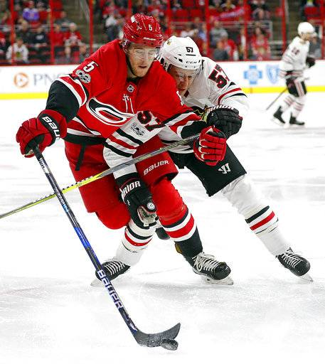 Carolina Hurricanes' Noah Hanifin (5) tangles with Chicago Blackhawks' Tommy Wingels (57) during the first period of an NHL hockey game, Saturday, Nov. 11, 2017, in Raleigh, N.C.