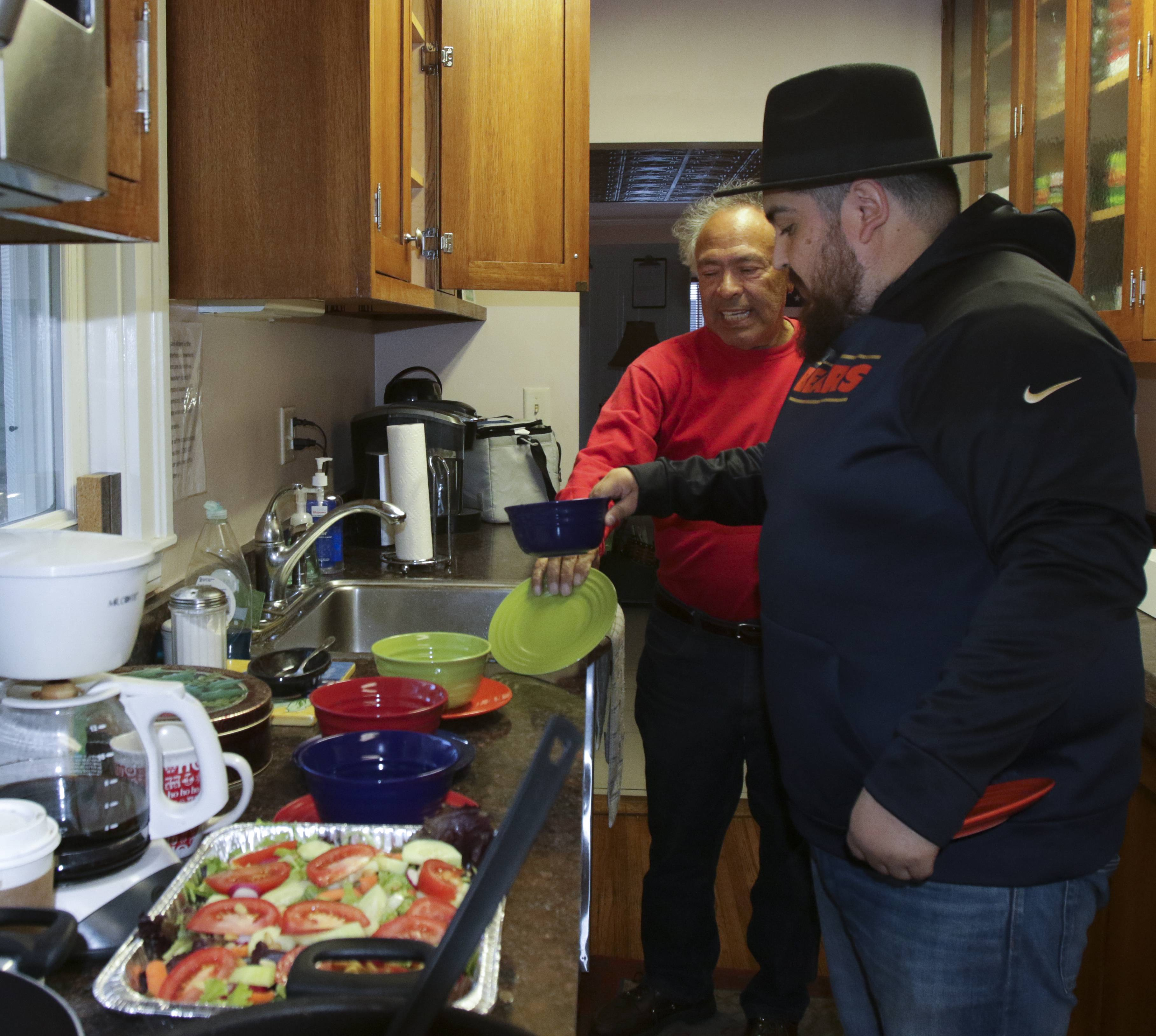 Manuel Lopez of Naperville, left, the father of a Marines veteran, left, helps house manager Alex Garcia in the kitchen of the Midwest Shelter for Homeless Veterans in Wheaton. Lopez promotes veterans suicide prevention and mental health awareness as a way to give back and thank those who served, like his son, Matthew.