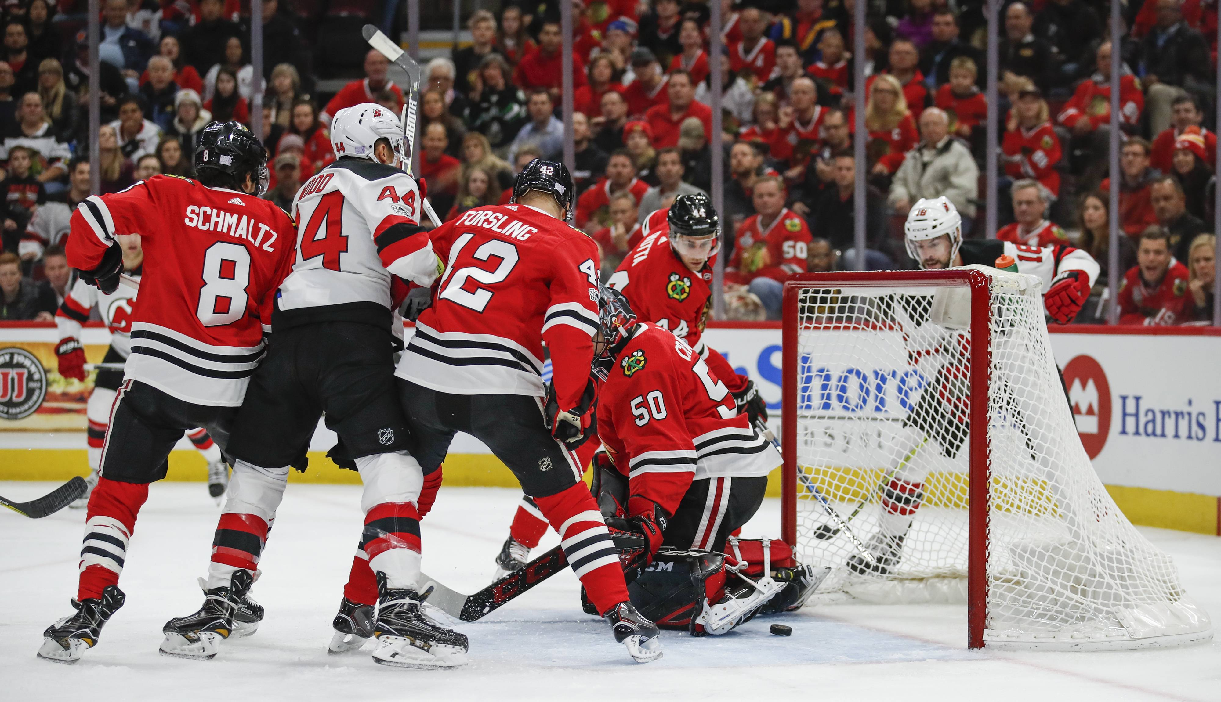 New Jersey Devils left wing Miles Wood scores against Chicago Blackhawks goalie Corey Crawford during the first period Sunday in Chicago.