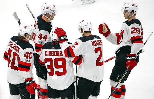 New Jersey Devils left wing Brian Gibbons (39) celebrates with teammates after scoring against the Chicago Blackhawks during the second period of an NHL hockey game Sunday, Nov. 12, 2017, in Chicago.
