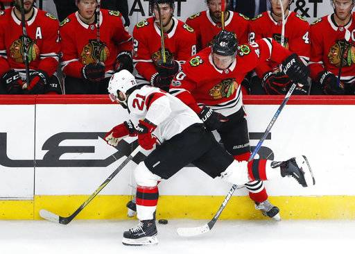 New Jersey Devils right wing Kyle Palmieri (21) battles for the puck with Chicago Blackhawks right wing John Hayden (40) during the second period of an NHL hockey game Sunday, Nov. 12, 2017, in Chicago.