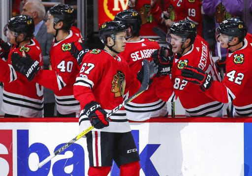 Chicago Blackhawks center Tanner Kero (67) celebrates with teammates after scoring against the New Jersey Devils during the first period of an NHL hockey game, Sunday, Nov. 12, 2017, in Chicago.