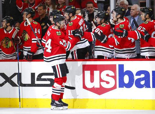 Chicago Blackhawks defenseman Jan Rutta (44) celebrates with teammates after scoring against the New Jersey Devils during the first period of an NHL hockey game, Sunday, Nov. 12, 2017, in Chicago.