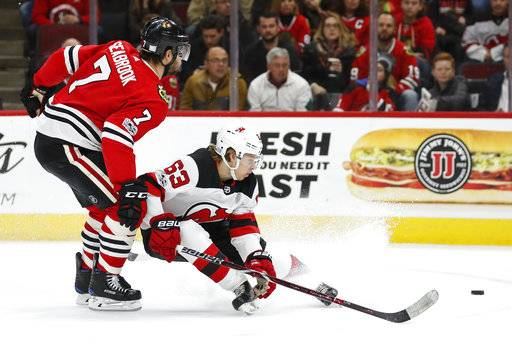 New Jersey Devils left wing Jesper Bratt (63) keeps the puck away from Chicago Blackhawks defenseman Brent Seabrook (7) during the first period of an NHL hockey game Sunday, Nov. 12, 2017, in Chicago.