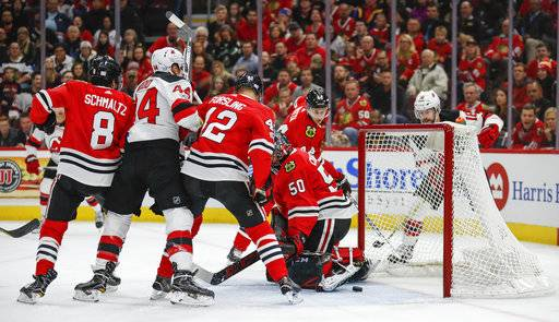 New Jersey Devils left wing Miles Wood (44) scores against Chicago Blackhawks goalie Corey Crawford (50) during the first period of an NHL hockey game Sunday, Nov. 12, 2017, in Chicago.