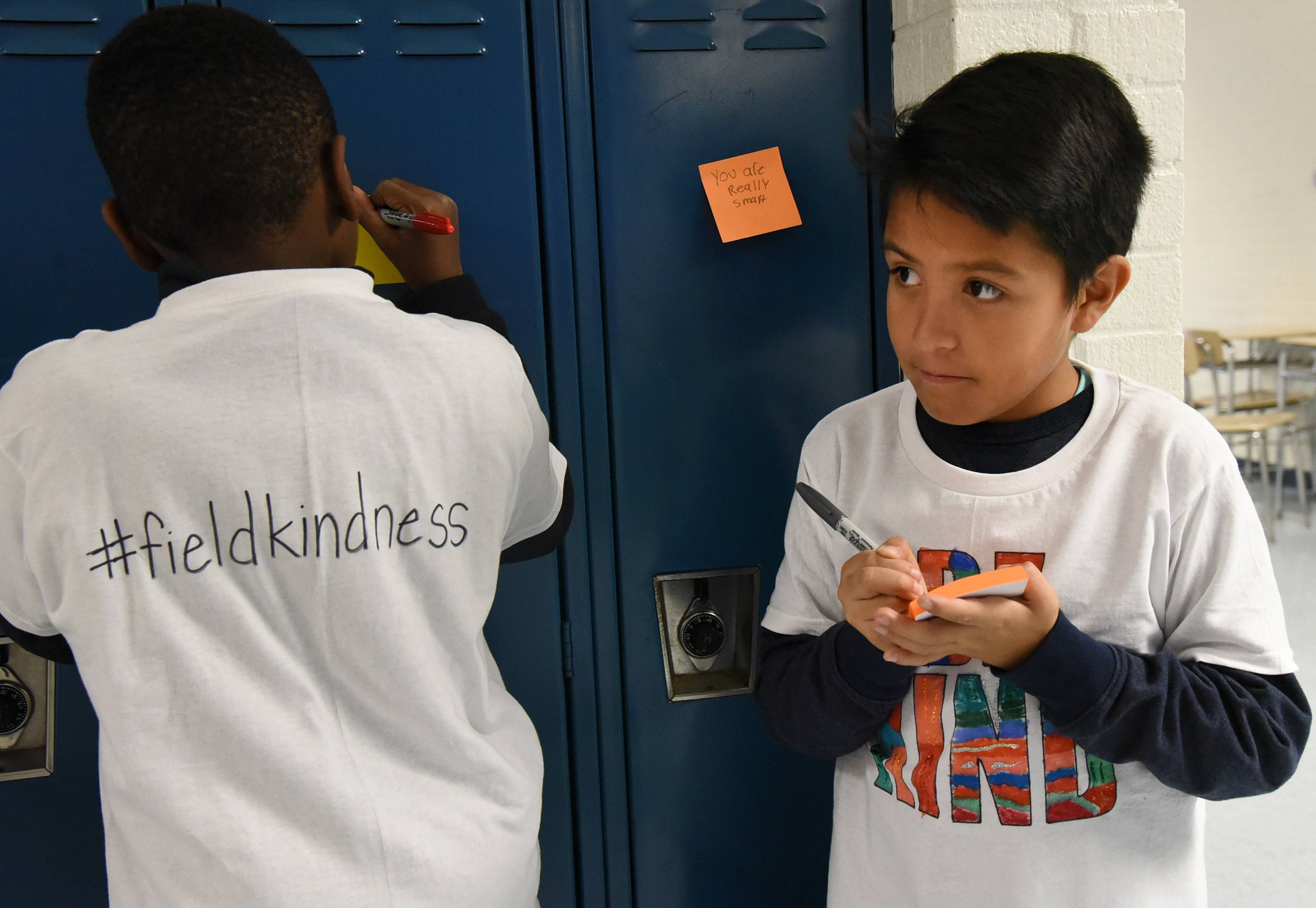 Jesus Altamirano, a fourth-grader at Field Elementary School in Wheeling, writes on a Post-it note to stick on a locker Monday at London Middle School as part of World Kindness Day.