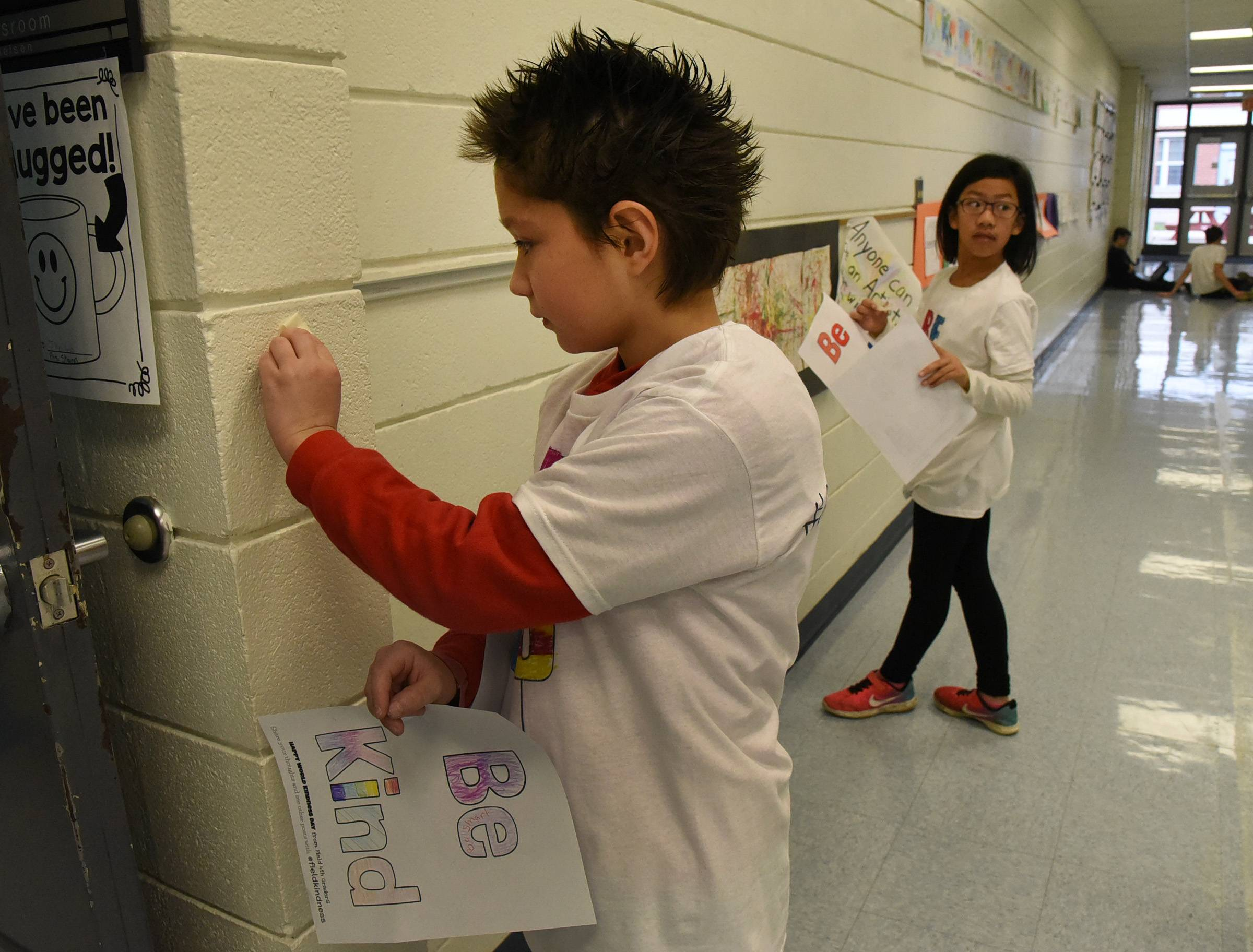 "Jaydon Young, a fourth-grader at Field Elementary School in Wheeling, applies a ""Be Kind"" sign in a hallway Monday at London Middle School. Field students have done a weekly kindness challenge this school year."