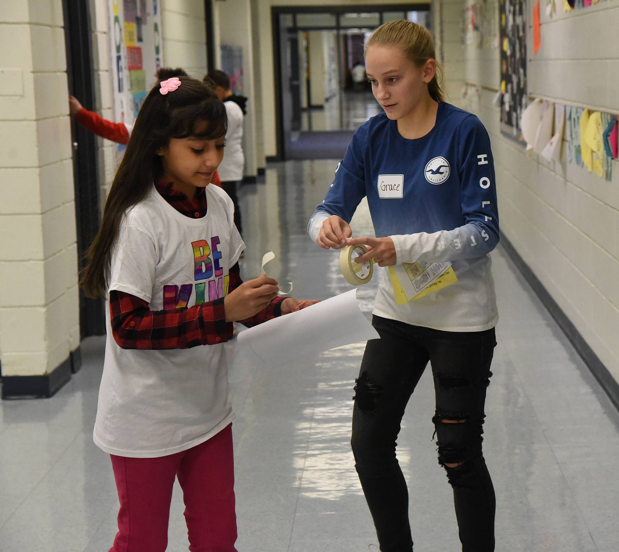 London Middle School eighth-grader Grace Veller helps Field Elementary School fourth-grader Ashley Martinez with her sign Monday at London. Field students came to post cheerful signs as part of World Kindness Day.