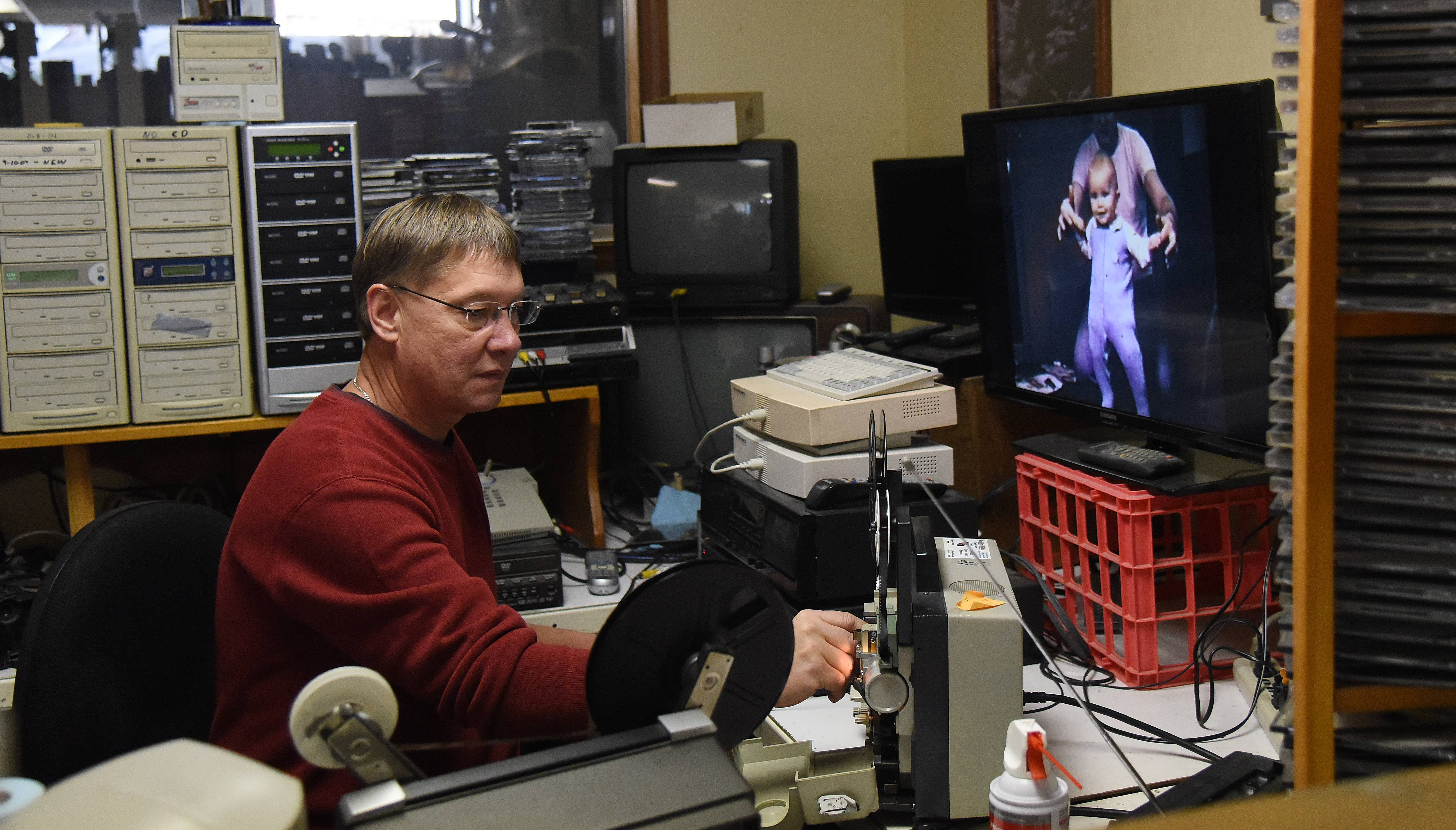 Brian LaVoy converts an old 8 mm film to digital media at Reel Pro Video in Batavia Monday. LaVoy is the new owner of the business, as his father Richard recently retired.