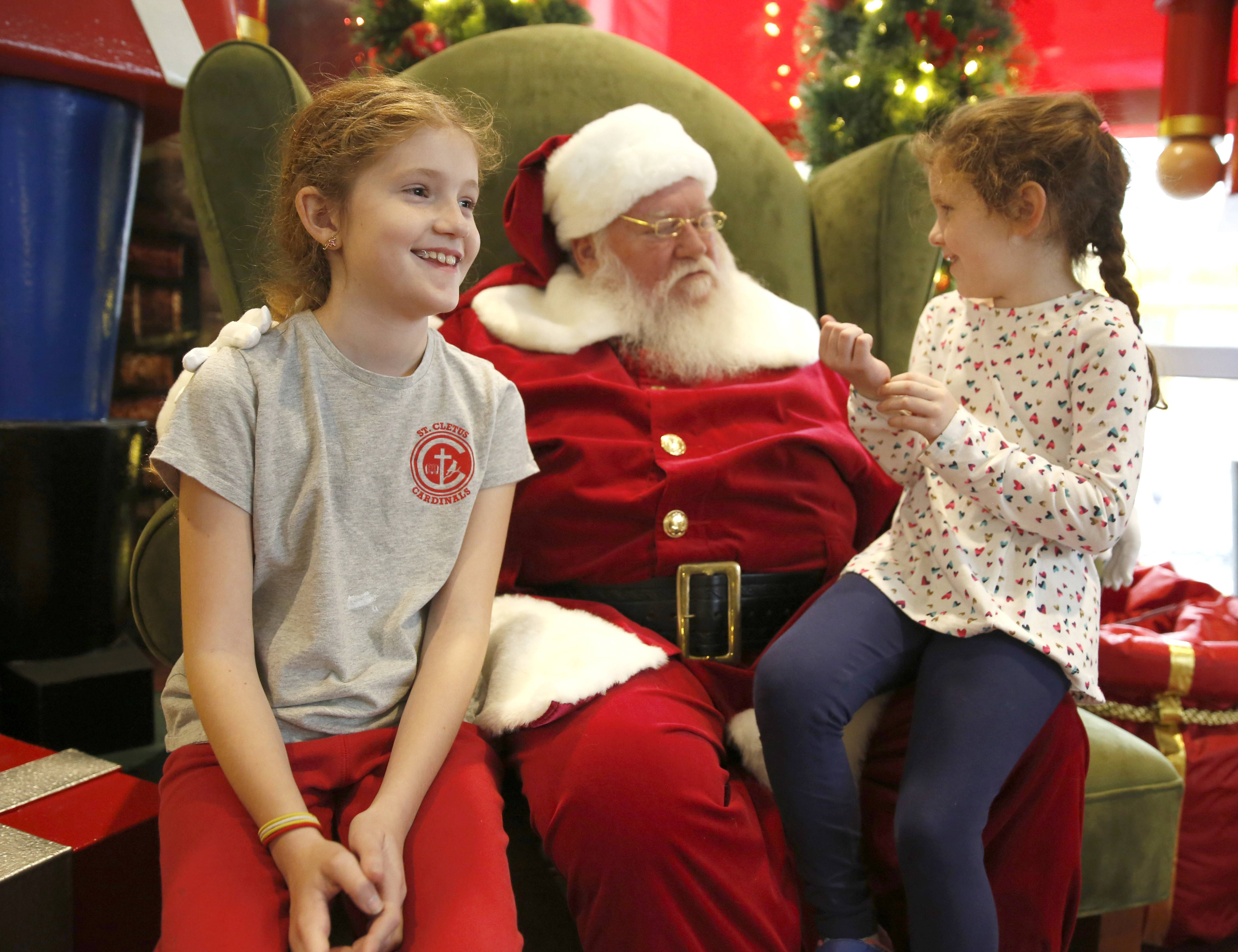 Lucy Ferron, 9, and Roxanne Ferron, 6, of Hickory Hills, visit Santa at Oakbrook Center's glass pavilion.