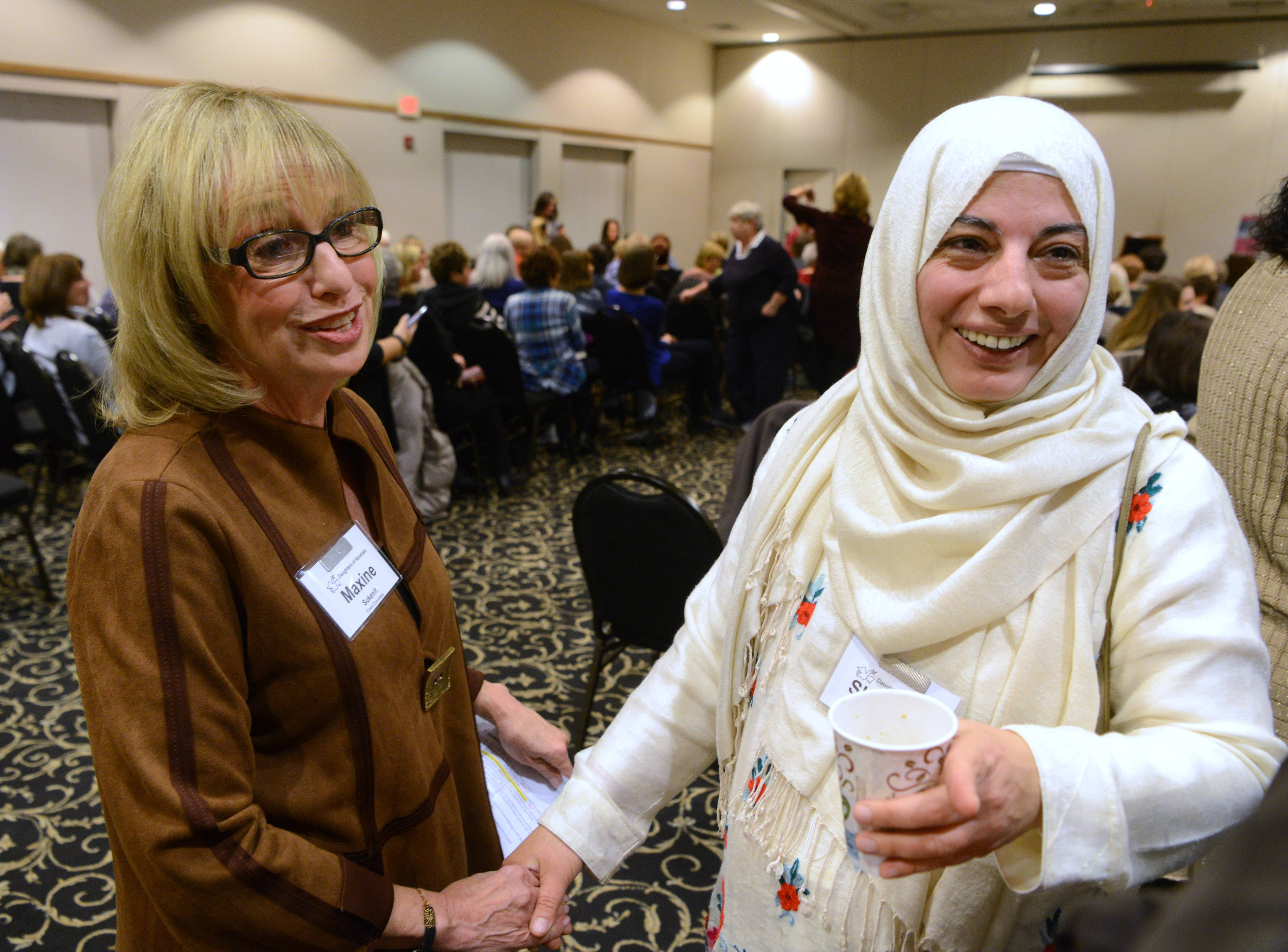 Maxine Sukenik, left, of Lincolnshire and Shaheen Khan of Wheeling greet one another at a gathering of the newly-formed interfaith group Daughters of Abraham at Temple Chai in Long Grove.